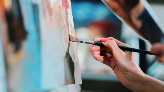 A close-up photo of someone painting on a canvas.